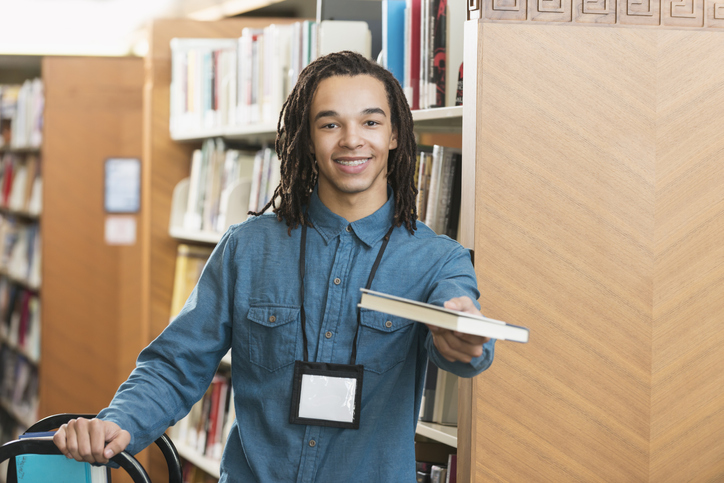 A young man working at the library, smiling at the camera, holding out a book. He is standing by the bookshelves with cart. He is mixed race, African American, with dreadlocks.