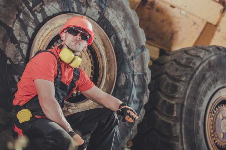Mine Dump Truck Operator. Caucasian Worker Seating Side to His Heavy Duty Truck.