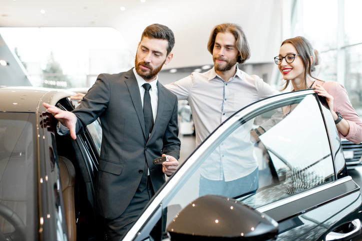 Salesman with couple in the car showroom