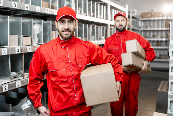 Warehouse workers with boxes indoors