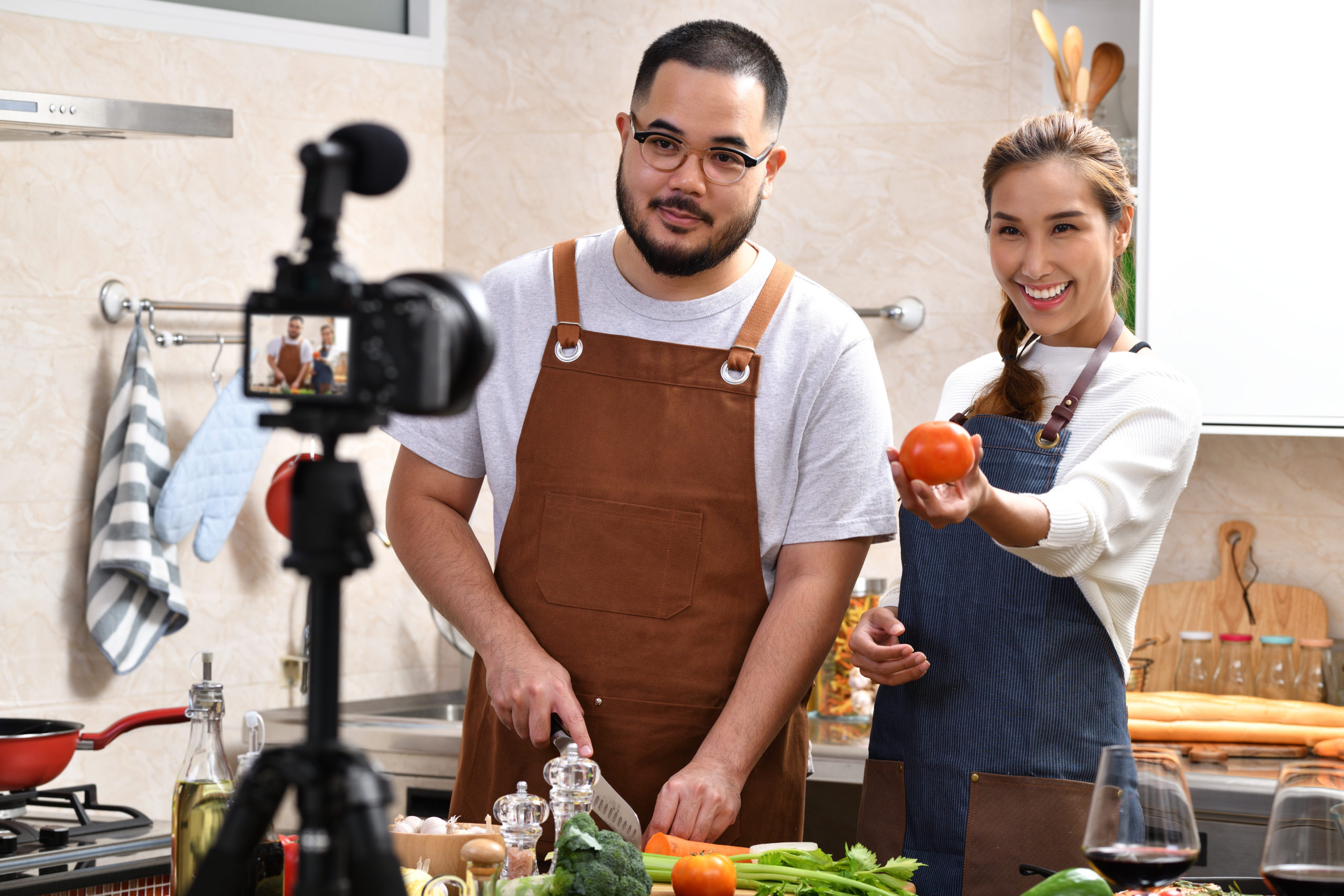 Young Asian couple blogger vlogger and online influencer recording video content on healthy food in the kitchen.